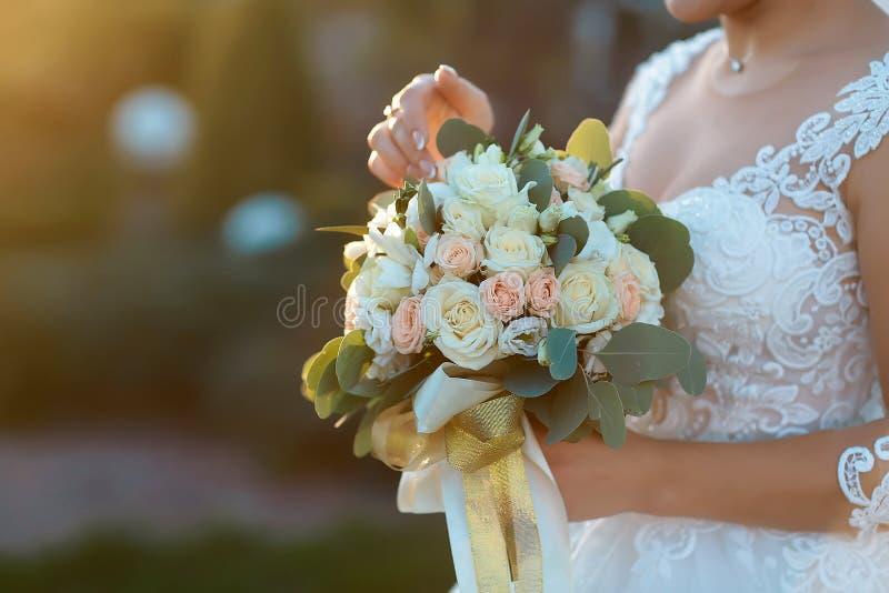 Νύφη που επιδεικνύει την όμορφη ανθοδέσμη λουλουδιών boho της στο ηλιοβασίλεμα Τέλεια εικόνα με το διάστημα αντιγράφων για: κομψά στοκ φωτογραφία με δικαίωμα ελεύθερης χρήσης