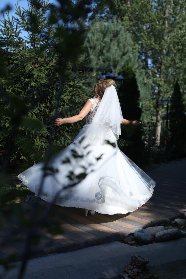 Νύφη που κάνει pirouette στο πάρκο στοκ φωτογραφίες
