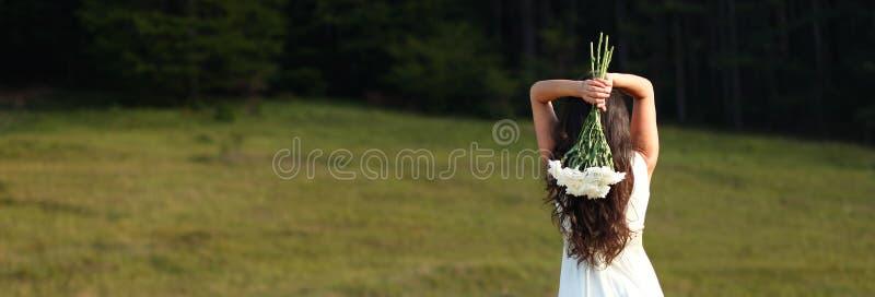 Νύφη που κρατά την άσπρη ανθοδέσμη υπερυψωμένη στη φύση στοκ εικόνες με δικαίωμα ελεύθερης χρήσης