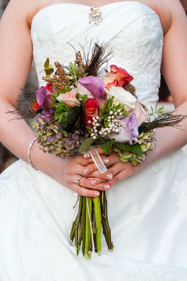 Νύφη που κρατά τη γαμήλια ανθοδέσμη της με την πορφύρα, το κόκκινο, και τα άσπρα λουλούδια στοκ φωτογραφία