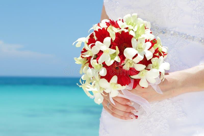 Νύφη που κρατά τη νυφική ανθοδέσμη στο φυσικό υπόβαθρο θάλασσας στοκ εικόνες με δικαίωμα ελεύθερης χρήσης
