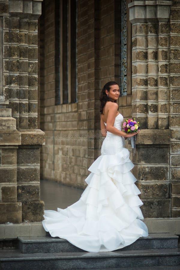 Νύφη που στέκεται ενάντια στον τοίχο με μια γαμήλια ανθοδέσμη των λουλουδιών στοκ εικόνες