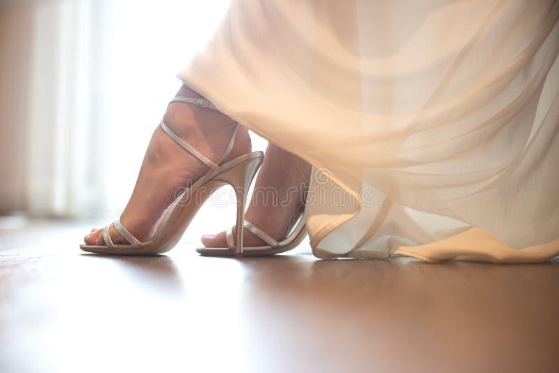 Νύφη που φορά τα γαμήλια παπούτσια Λεπτομέρειες κινηματογραφήσεων σε πρώτο πλάνο των ποδιών νυφών που φορούν τα παπούτσια στοκ εικόνα με δικαίωμα ελεύθερης χρήσης