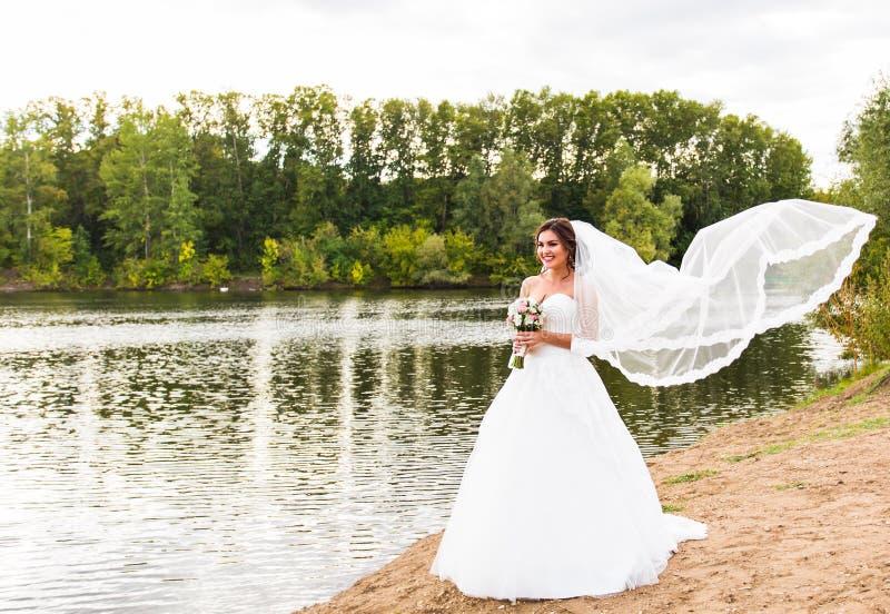 Νύφη σε ένα άσπρο φόρεμα με τη γαμήλια ανθοδέσμη στη λίμνη στοκ φωτογραφία με δικαίωμα ελεύθερης χρήσης