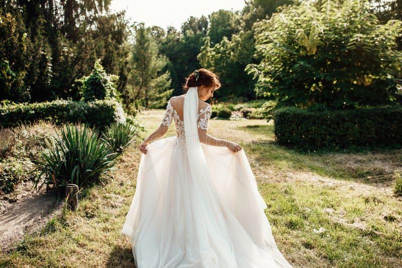 Νύφη σε ένα φόρεμα που στέκεται σε έναν πράσινο κήπο και που κρατά ένα weddin στοκ εικόνες