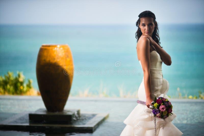 Νύφη σε μια πολυτελή άσπρη τοποθέτηση φορεμάτων ενάντια στη θάλασσα στοκ φωτογραφίες με δικαίωμα ελεύθερης χρήσης