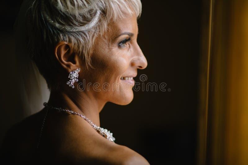 Νύφη στα συμπαθητικά σκουλαρίκια δίπλα στο παράθυρο στοκ εικόνα με δικαίωμα ελεύθερης χρήσης
