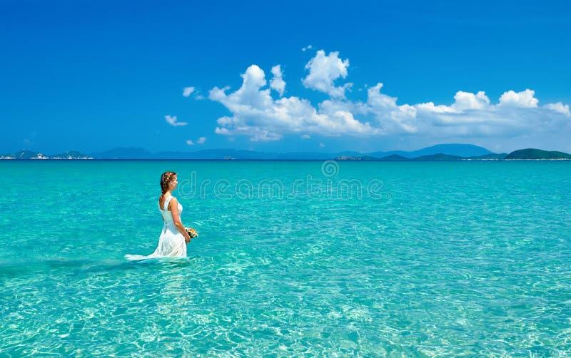 Νύφη στην παραλία που περπατά στο νερό στοκ εικόνες με δικαίωμα ελεύθερης χρήσης