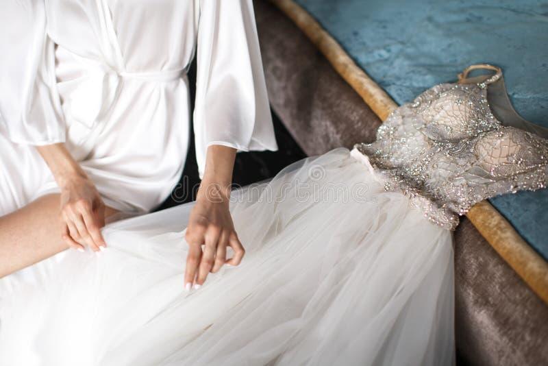 Νύφη στην τήβεννο δαντελλών και weding φόρεμα στο κρεβάτι στοκ εικόνες