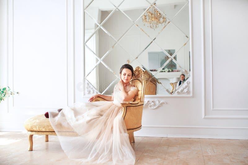 Νύφη στην όμορφη συνεδρίαση φορεμάτων στον καναπέ στο εσωτερικό στο άσπρο εσωτερικό στούντιο όπως στο σπίτι Καθιερώνον τη μόδα γα στοκ εικόνα με δικαίωμα ελεύθερης χρήσης