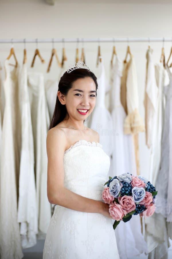 Νύφη στη γαμήλια ανθοδέσμη εκμετάλλευσης φορεμάτων των λουλουδιών και της πρασινάδας, ευτυχής γαμήλια έννοια στοκ φωτογραφίες