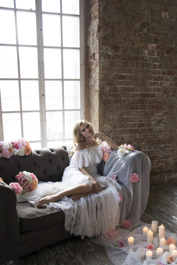 Νύφη στον εκλεκτής ποιότητας καναπέ με τα λουλούδια και τα κεριά στοκ φωτογραφίες με δικαίωμα ελεύθερης χρήσης