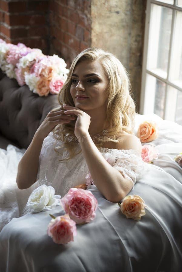Νύφη στον εκλεκτής ποιότητας καναπέ με τα λουλούδια στοκ εικόνα με δικαίωμα ελεύθερης χρήσης