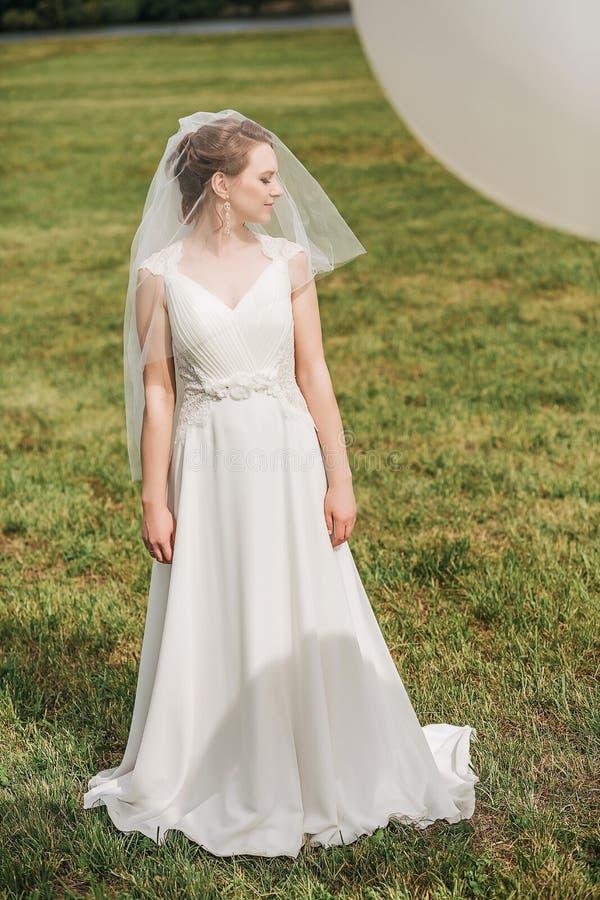 Νύφη στο άσπρο φόρεμα που στέκεται στο πράσινο λιβάδι στοκ εικόνα