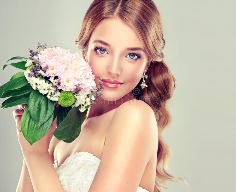 Νύφη στο γαμήλιο φόρεμα με την ανθοδέσμη λουλουδιών στοκ εικόνα