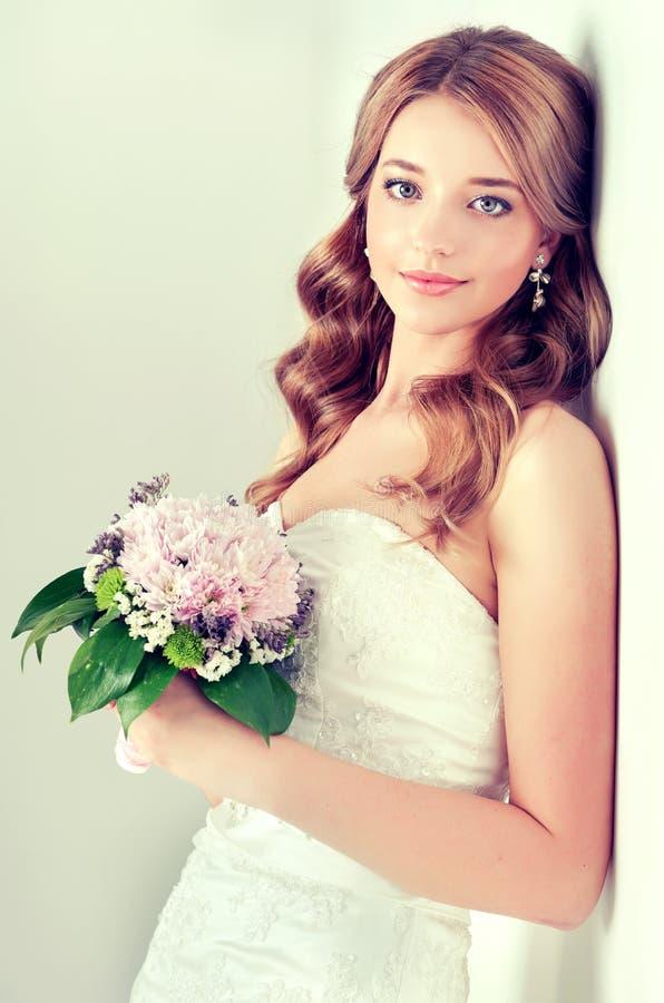 Νύφη στο γαμήλιο φόρεμα με την ανθοδέσμη λουλουδιών στοκ φωτογραφία με δικαίωμα ελεύθερης χρήσης