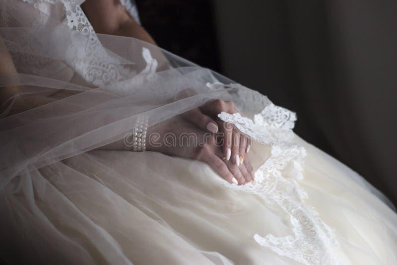 νύφη στο γαμήλιο φόρεμα σε ένα σκοτεινό δωμάτιο ι στοκ εικόνες