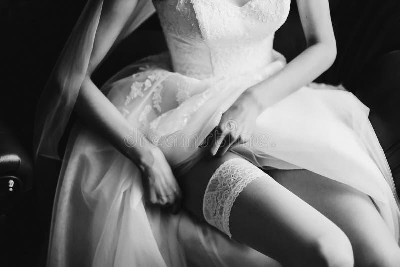 Νύφη στο κομψές κλασικές γαμήλιες φόρεμα και τις γυναικείες κάλτσες Πρωί της νύφης στοκ εικόνα με δικαίωμα ελεύθερης χρήσης