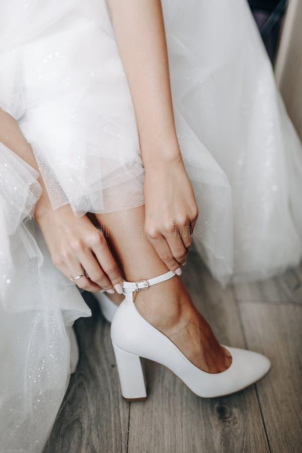 Νύφη στο όμορφο γαμήλιο φόρεμα που βάζει στα παπούτσια στοκ εικόνα