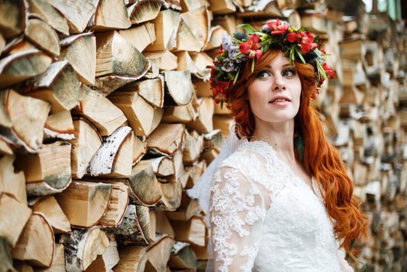 Νύφη Boho με την κόκκινη τρίχα με τα λουλούδια στοκ εικόνες