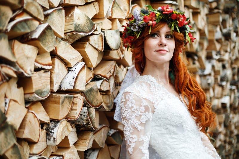 Νύφη Boho με την κόκκινη τρίχα με τα λουλούδια στοκ φωτογραφία