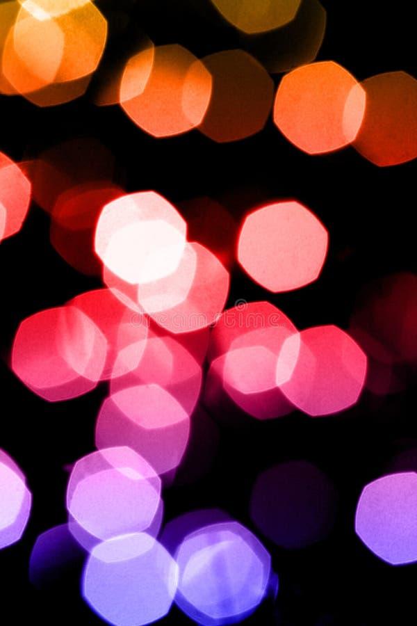 Νύχτα ή εορταστική έννοια κομμάτων: το αφηρημένο υπόβαθρο ακτινοβολεί φωτεινά φω'τα bokeh στοκ εικόνα