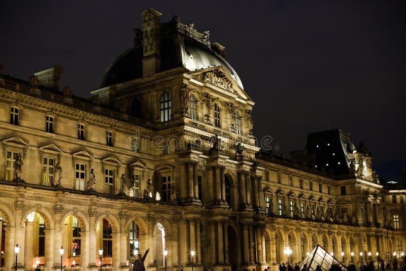 Νύχτα που καταπλήσσει το Λούβρο και τους τουρίστες που περπατούν στο Παρίσι, Γαλλία στοκ φωτογραφία