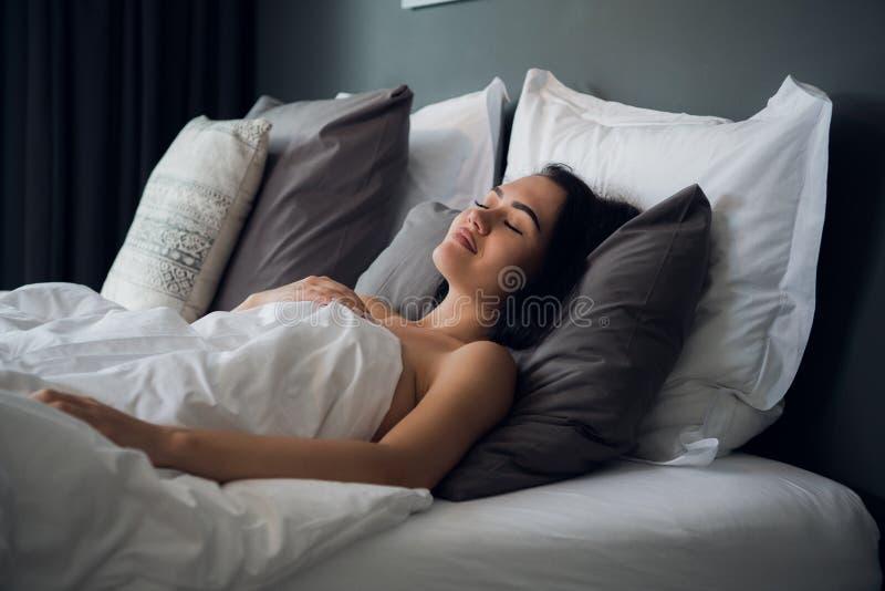 Νύχτα, υπόλοιπο, άνεση και έννοια ανθρώπων - νέος ύπνος γυναικών στο κρεβάτι στο σπίτι στοκ εικόνα