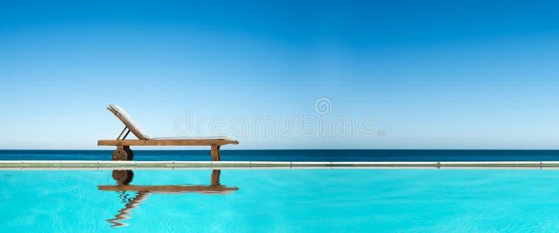 Ξάπλωμα της καρέκλας κοντά σε μια πισίνα, πανοραμικό υπόβαθρο μπλε ουρανού θάλασσας στοκ φωτογραφίες με δικαίωμα ελεύθερης χρήσης