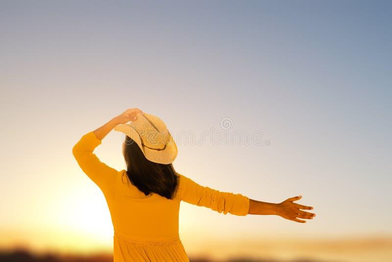 Ξένοιαστη νέα γυναίκα που εξετάζει το ηλιοβασίλεμα στοκ εικόνα