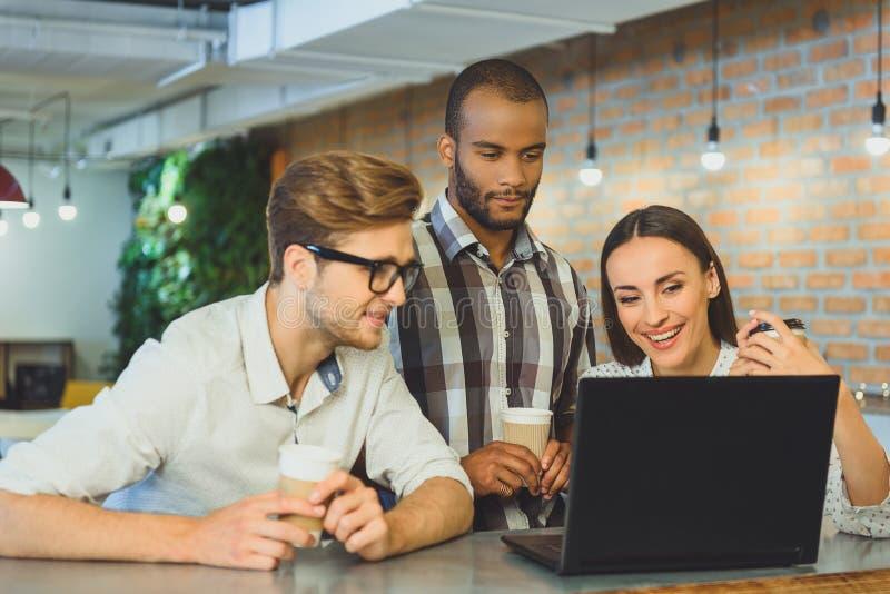 Ξένοιαστοι άνδρες και γυναίκα που χρησιμοποιούν το lap-top στην καφετέρια στοκ εικόνες
