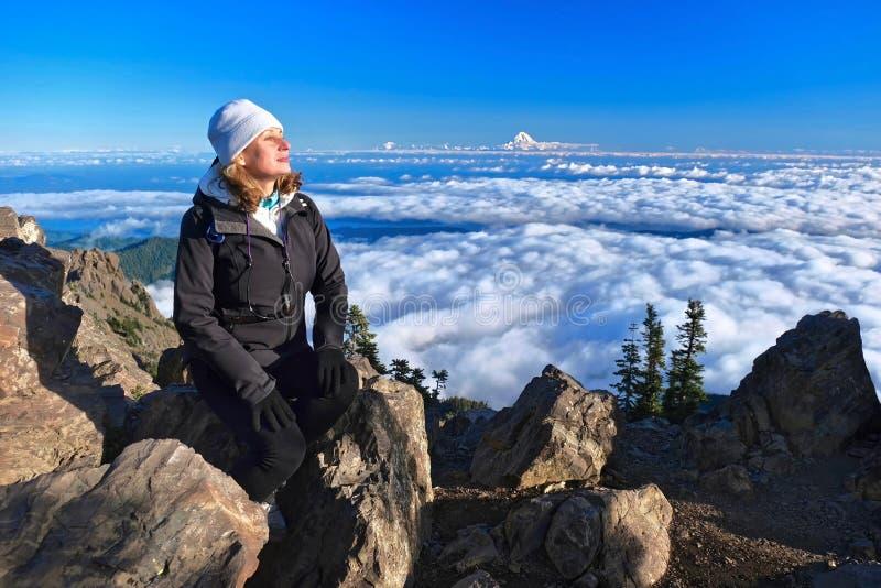 Ξένοιαστος οδοιπόρος γυναικών στην κορυφή βουνών με την πιό βροχερή άποψη υποστηριγμάτων σχετικά με τον ορίζοντα στοκ εικόνες