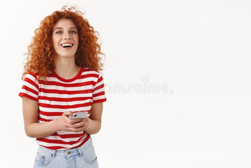 Ξένοιαστο πανέμορφο εξερχόμενο νέο σύγχρονο redhead κορίτσι 25s που χρησιμοποιεί το texting λευκό ευτυχώς χαμόγελου φίλων smartph στοκ φωτογραφία