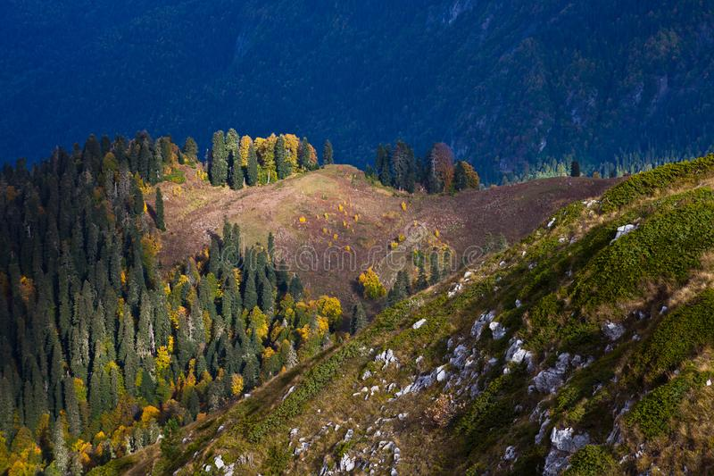 Ξέφωτο στην άκρη ενός οροπέδιου βουνών, που φωτίζεται από τον ήλιο και η λίμνη κατωτέρω στοκ φωτογραφία με δικαίωμα ελεύθερης χρήσης