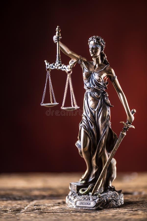 Ξίφος γυναικείας Justicia εκμετάλλευσης και ειδώλιο χαλκού κλίμακας σε ξύλινο στοκ φωτογραφία