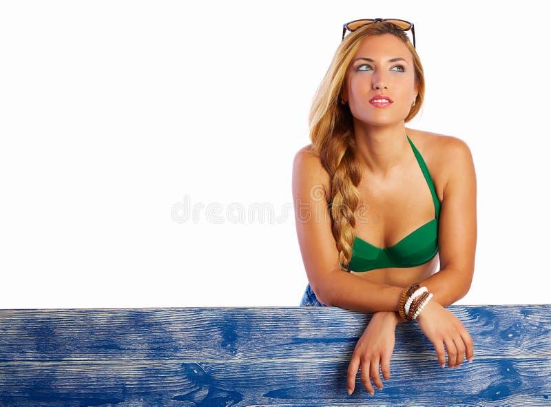 Ξανθά διασχισμένα κορίτσι όπλα μπικινιών στον μπλε ξύλινο φράκτη στοκ φωτογραφία με δικαίωμα ελεύθερης χρήσης