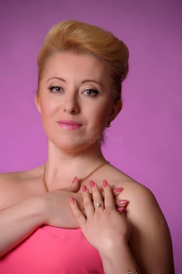 Ξανθά σαράντα χρονών στο στούντιο στο ροζ με το hairdo βραδιού στοκ φωτογραφία