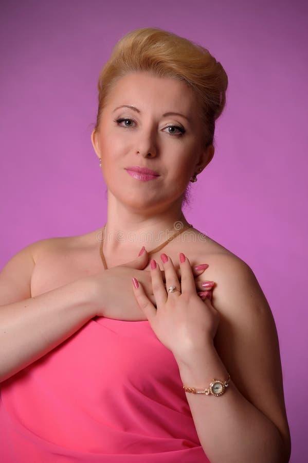 Ξανθά σαράντα χρονών στο στούντιο στο ροζ με το hairdo βραδιού στοκ φωτογραφίες με δικαίωμα ελεύθερης χρήσης