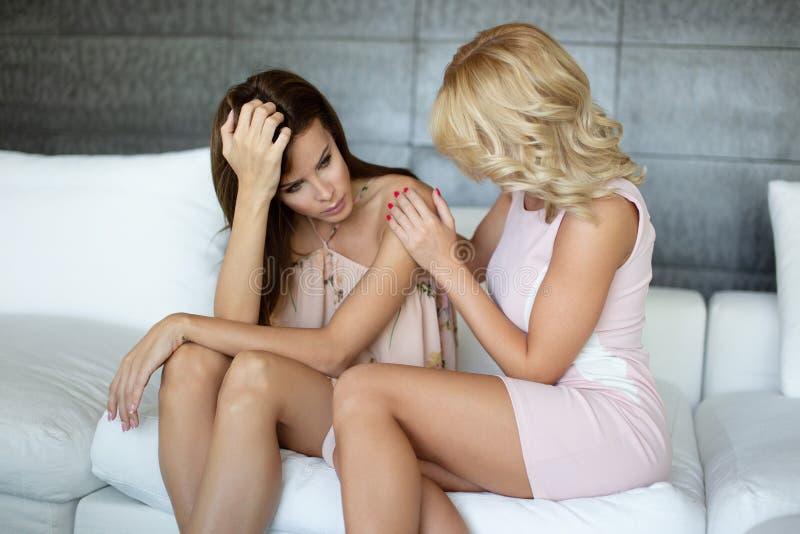 Ξανθές βοήθειες γυναικών Empathic στη φίλη με τα προβλήματά της στοκ εικόνα με δικαίωμα ελεύθερης χρήσης