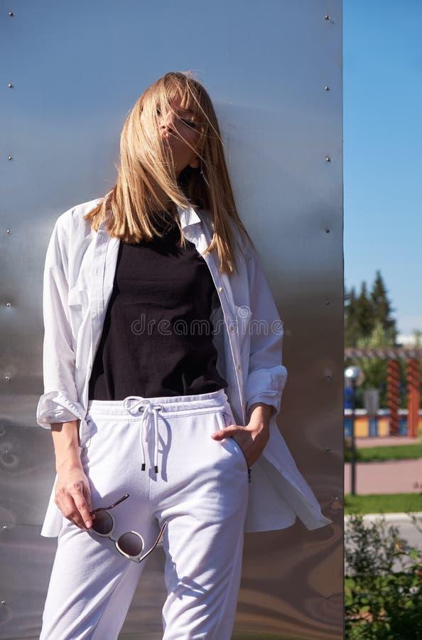 ξανθές νεολαίες γυναικών Θηλυκή πρότυπη τοποθέτηση στο υπόβαθρο μετάλλων στοκ φωτογραφία με δικαίωμα ελεύθερης χρήσης