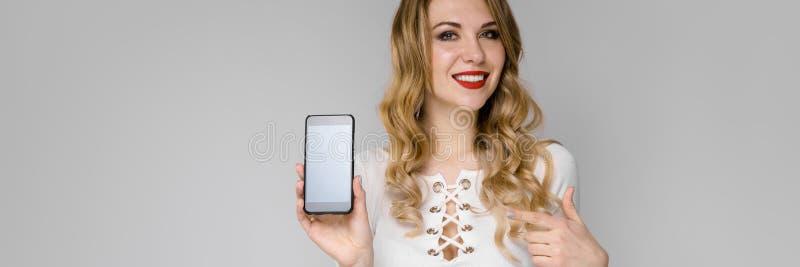 ξανθές νεολαίες πορτρέτ&omicron Νέο κορίτσι που κρατά ένα τηλέφωνο στο χέρι της στοκ εικόνα με δικαίωμα ελεύθερης χρήσης