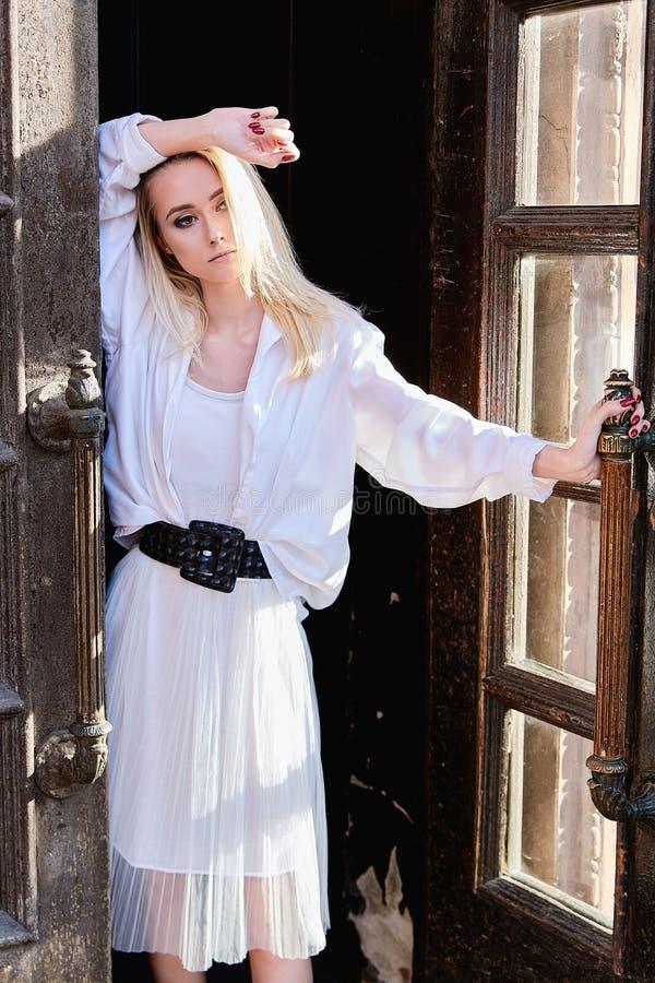 Ξανθές στάσεις γυναικών στην παλαιά ξύλινη πόρτα Η παλαιά ξύλινη πόρτα r στοκ φωτογραφία με δικαίωμα ελεύθερης χρήσης