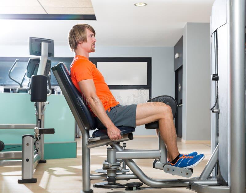 Ξανθή άσκηση ατόμων απαγωγής ισχίων στο κλείσιμο γυμναστικής στοκ φωτογραφία