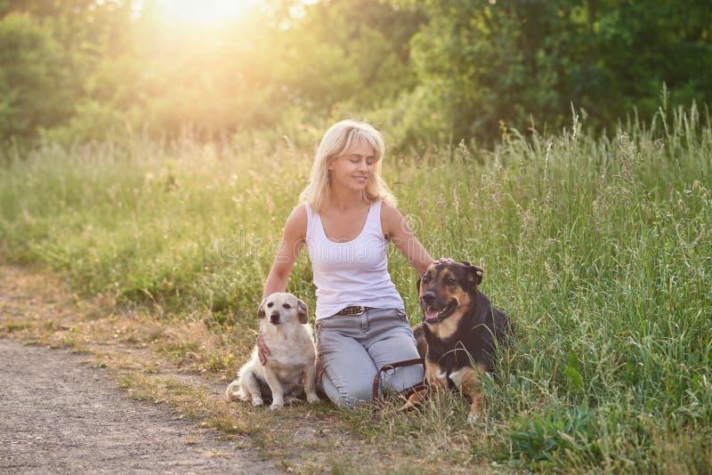 Ξανθή γυναίκα με δύο σκυλιά της στην επαρχία στοκ φωτογραφίες