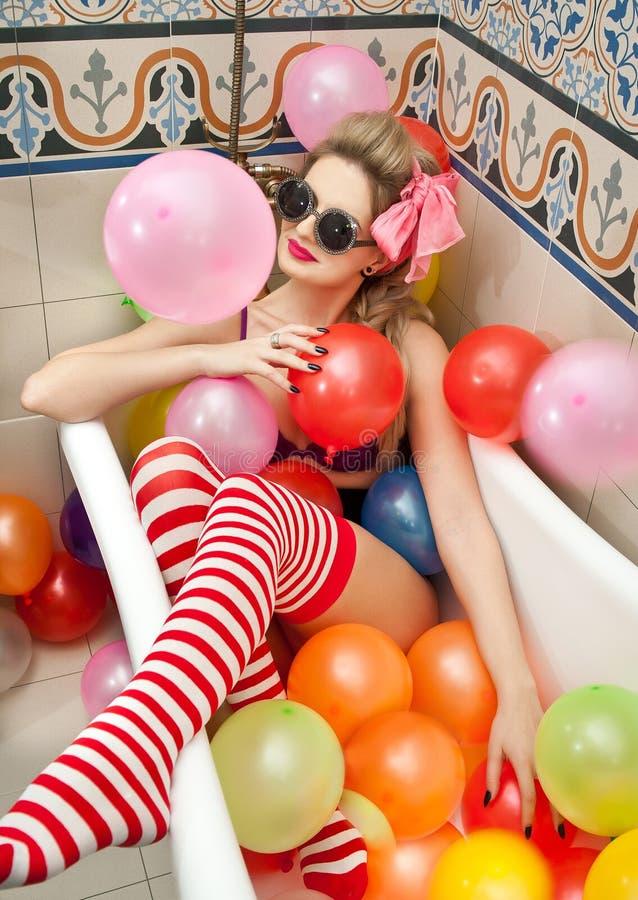 Ξανθή γυναίκα με τα γυαλιά ηλίου που παίζει στο σωλήνα λουτρών της με τα φωτεινά χρωματισμένα μπαλόνια Αισθησιακό κορίτσι με τις  στοκ φωτογραφίες