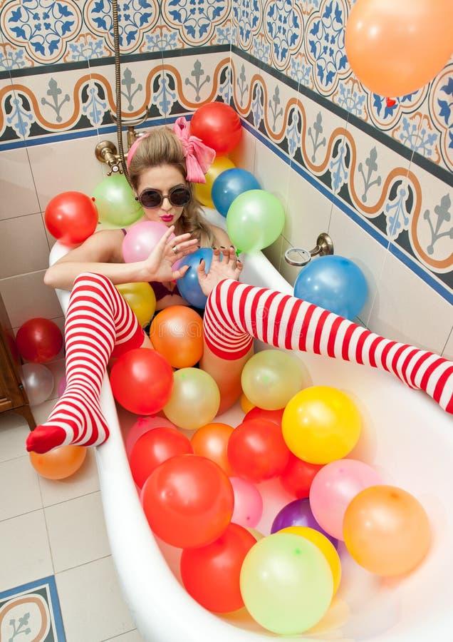 Ξανθή γυναίκα με τα γυαλιά ηλίου που παίζει στο σωλήνα λουτρών της με τα φωτεινά χρωματισμένα μπαλόνια Αισθησιακό κορίτσι με τις  στοκ εικόνα