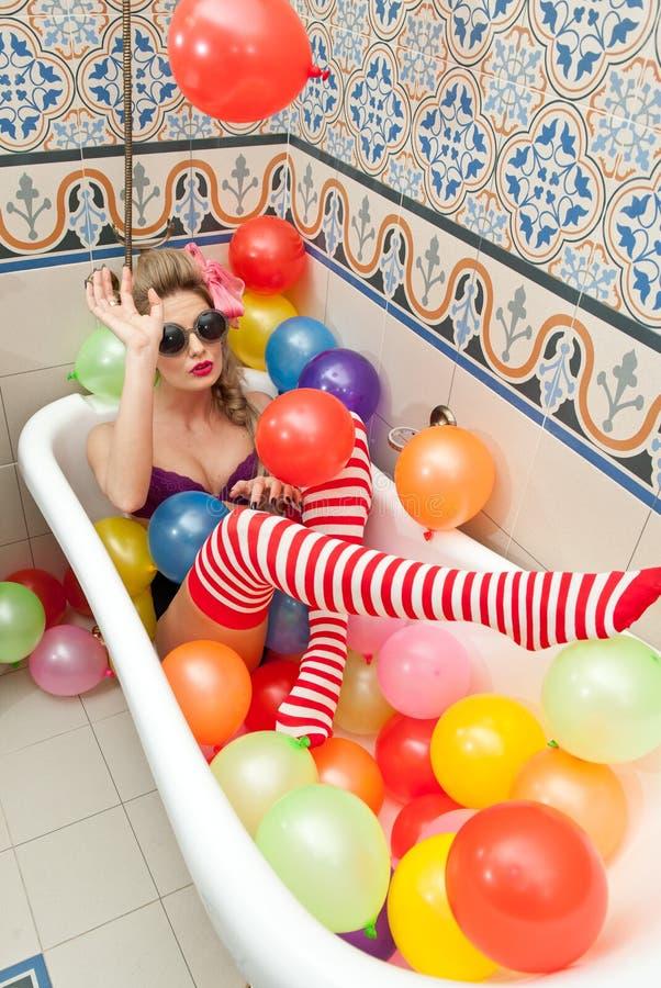 Ξανθή γυναίκα με τα γυαλιά ηλίου που παίζει στο σωλήνα λουτρών της με τα φωτεινά χρωματισμένα μπαλόνια Αισθησιακό κορίτσι με τις  στοκ εικόνα με δικαίωμα ελεύθερης χρήσης