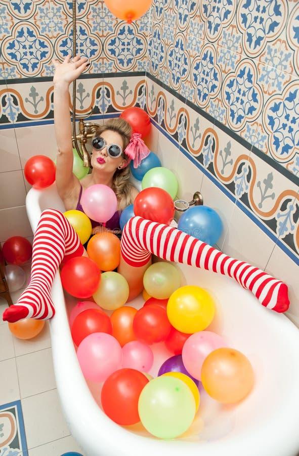 Ξανθή γυναίκα με τα γυαλιά ηλίου που παίζει στο σωλήνα λουτρών της με τα φωτεινά χρωματισμένα μπαλόνια Αισθησιακό κορίτσι με τις  στοκ εικόνες με δικαίωμα ελεύθερης χρήσης