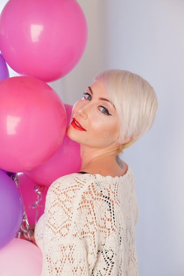 Ξανθή γυναίκα με τα μπαλόνια και τα δώρα για τις διακοπές στοκ εικόνες