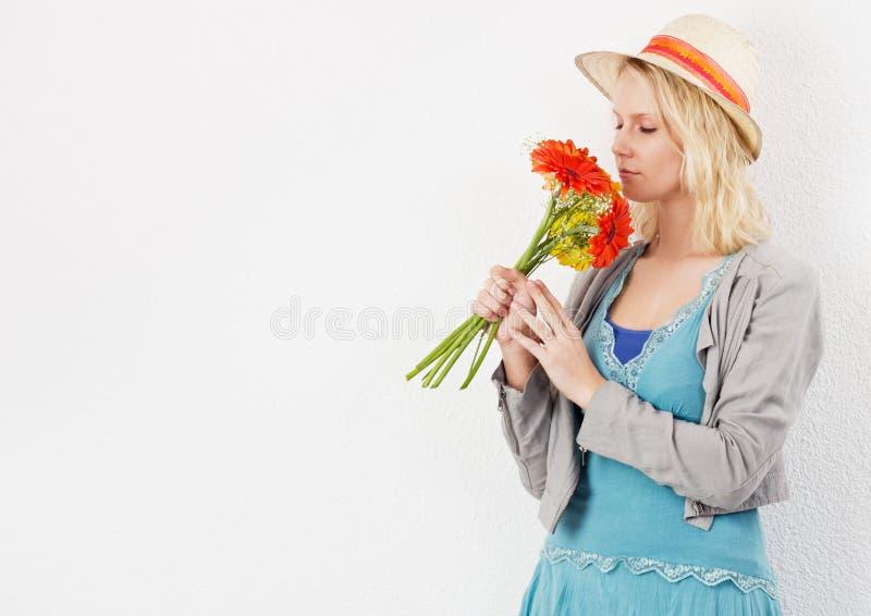 Ξανθή γυναίκα με τα μυρίζοντας λουλούδια καπέλων ήλιων στοκ φωτογραφία με δικαίωμα ελεύθερης χρήσης